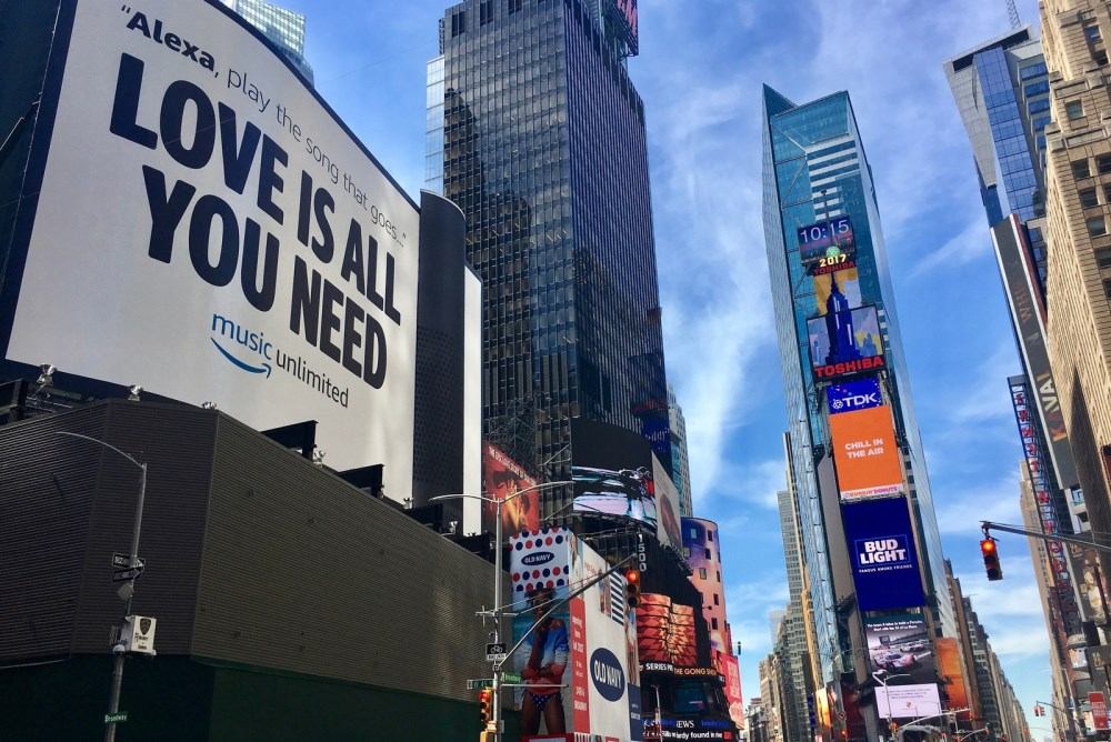 A Giant Amazon Echo Towers Over Onlookers In Times Square